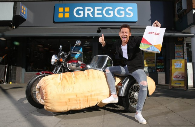 EDITORIAL USE ONLY A 'Sausage Roll-Mobile', featuring a sidecar in the shape of a sausage roll, is unveiled by actor Joe Swash as it hits the road in London to celebrate Greggs now being available on online food delivery service, Just Eat. PRESS ASSOCIATION Photo. Issue date: Wednesday July 3, 2019. The partnership offers delivery of Greggs baked goods, with no minimum spend, in London, Newcastle and Glasgow via the Just Eat app or online. Photo credit should read: Matt Alexander/PA Wire