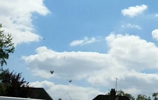 This bizarre footage shows clusters of dry grass falling from the sky in a phenomenon caused by the warm weather. See SWNS story SWSYgrass. Mum-of-two Tanya Rendall, 46, filmed the spectacle on Wednesday lunchtime as she left her home in Tewkesbury, Glos., to go to work. Experts at the Met Office believe the grass is from a recently cut field and has risen because the ground has heated the air above it. This causes the air to rise and carries the grass aloft.