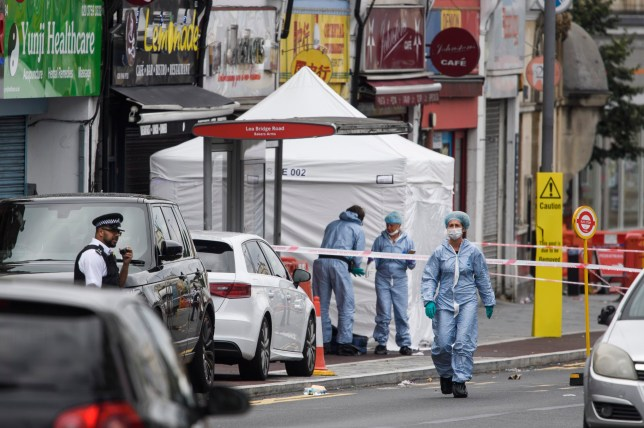 Police forensics at the scene where a man in his 20s has been shot dead in Leyton, East London in the early hours of this morning.