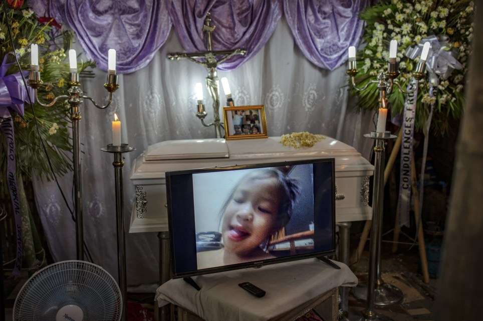 "RODRIGUEZ, PHILIPPINES - JULY 09: A screen flashes a picture of three-year-old Kateleen Myca Ulpina during her funeral wake on July 9, 2019 in Rodriguez, Rizal province, Philippines. Ulpina was shot dead last June 29 by police officers conducting a drug raid targeting her father, who police say was armed and used her daughter as a human shield. The three-year-old girl is one of the latest victims of President Rodrigo Duterte's controversial and bloody ""war on drugs"", which human rights groups estimate have left more than 27,000 mostly poor people killed. On Monday, Amnesty International described the drug war as a ""large-scale murdering enterprise"" and urged the United Nations to investigate for crimes against humanity. (Photo by Ezra Acayan/Getty Images)"