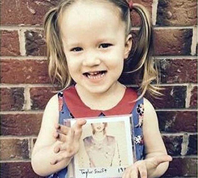 Violet-Grace poses against a wall holding a Taylor Swift CD
