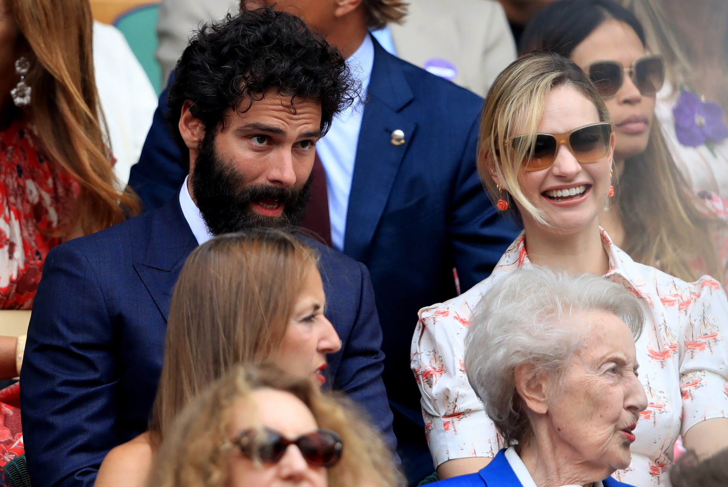 Aidan Turner and Lily James on day twelve of a Wimbledon Championships during a All England Lawn Tennis and Croquet Club, Wimbledon. PRESS ASSOCIATION Photo. Picture date: Saturday Jul 13, 2019. See PA story TENNIS Wimbledon. Photo credit should read: Adam Davy/PA Wire. RESTRICTIONS: Editorial use only. No blurb use but before created agree of a AELTC. Still picture use usually - no relocating images to obey broadcast. No superimposing or dismissal of sponsor/ad logos.