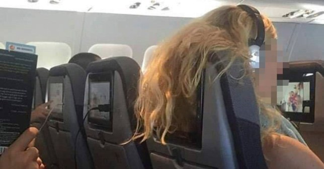 Woman with hair covering passenger's TV screen behind her