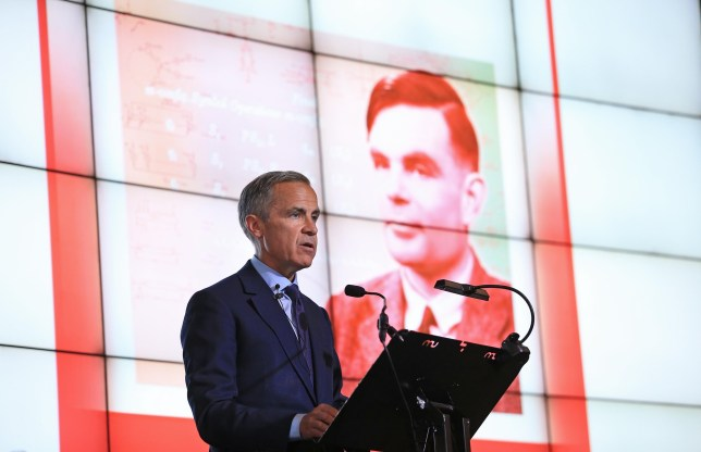 Mark Carney standing at a podium with the the new £50 note in the background, featuring Alan Turing