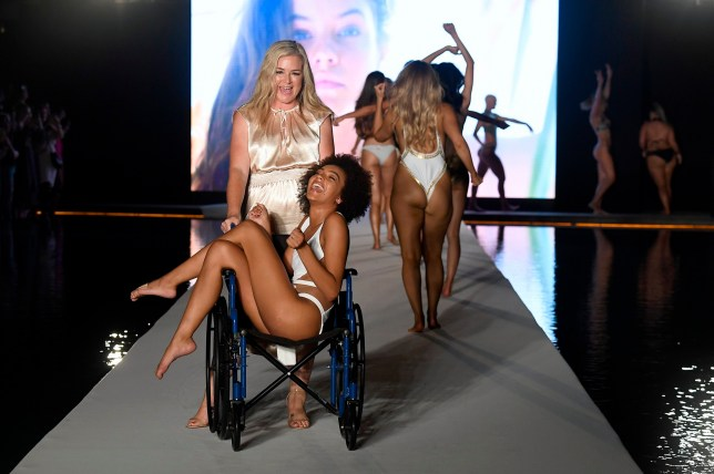 Model is wheeled down the runway on the Sports Illustrated catwalk