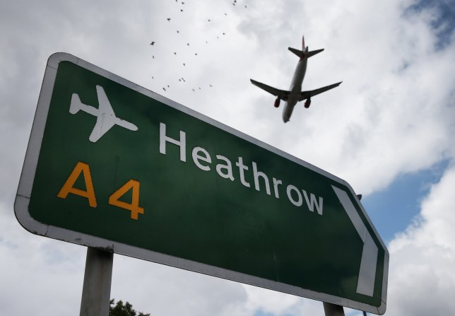 plane flying over heathrow airport sign