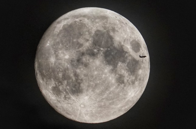 A plane passes the moon as it rises over Northumberland in north east England. PRESS ASSOCIATION Photo. Picture date: Monday July 15, 2019. Photo credit should read: Owen Humphreys/PA Wire