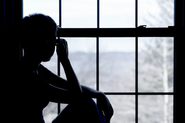 File photo of young girl in silhouette looking out of a window