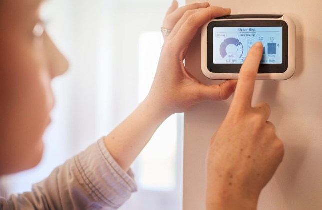 Close up of home owner checking energy consumption on smart meter home technology. She can see her energy consumption and billing all in one place and live costs. Graphics have been altered.