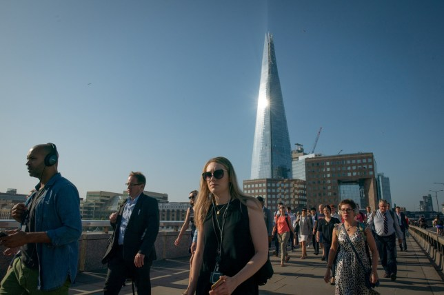 Commuters cross London Bridge, London, as temperatures are expected to get close to previous yearly records this week. 23 July 2019