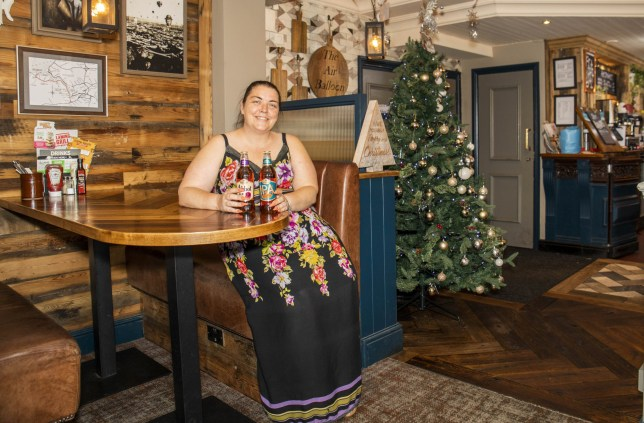 Joanne Johnson, the General Manager at The Air Balloon, a pub which has displayed and decorated a Christmas Tree in July. Bristol. 23 July 2019. See SWNS story SWBRtree. A pub has become the first in Britain to put its CHRISTMAS tree up - on the hottest day of summer. The five-foot artificial tree, adorned with gold, blue and silver baubles, has been installed at the Air Balloon pub in Bristol. The display - as Britain bakes in 37 degree heat - is complete with a sign at the foot of which reads: 'Have yourself a merry little Christmas'. And its lights are flashing brightly as it stands beside the bar.