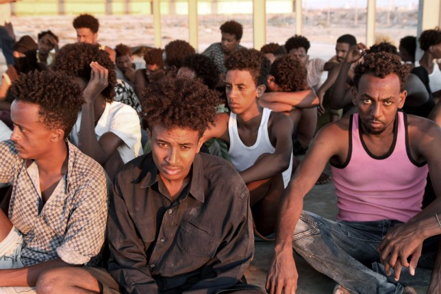 Rescued migrants sit on the coast of Khoms, some 100 kilometres (60 miles) from Tripoli, on July 26, 2019. - More than 100 migrants were missing after their boat sank off the coast of Libya in what might be the worst tragedy in the Mediterranean this year, aid agencies said. About 145 migrants were rescued by the Libyan coastguard, and survivors had reported that about 150 people remained missing. (Photo by - / AFP)-/AFP/Getty Images