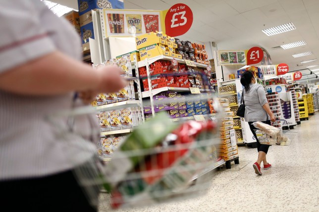 "Customers carry shopping baskets as they browse goods displayed for sale inside a Tesco Extra Supermarket, operated by Tesco Plc, in London, U.K., on Tuesday, July 1, 2014. Tesco Chief Executive Officer Philip Clarke asked shareholders last week for more time to complete ""radical"" changes, from altering shop formats to lowering prices"
