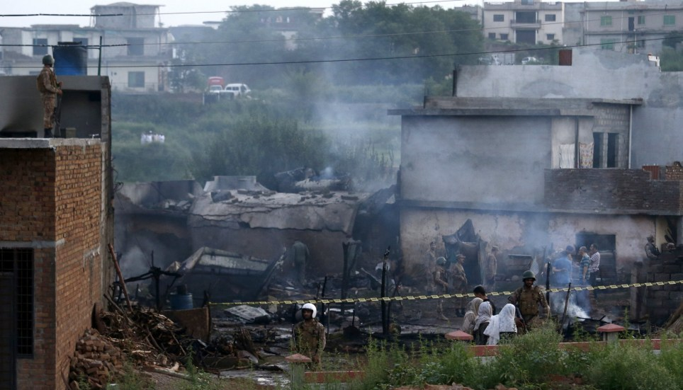 epa07748121 Pakistani security officials inspect the scene of a military plane crash on the outskirts of Rawalpindi, Pakistan, 30 July 2019. At least 17 people were killed and several others wounded when a small military plane crashed in a residential area on the outskirts of Rawalpindi. EPA/T. MUGHAL