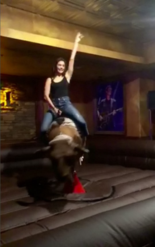 nina dobrev riding a mechanical bull