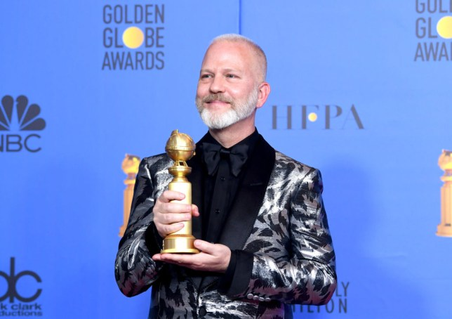 Ryan Murphy holding a Golden Globe