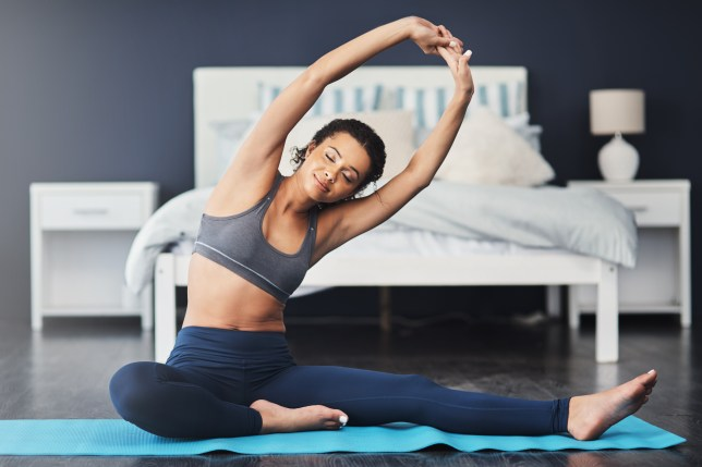 A woman doing yoga on a mat in her bedroom