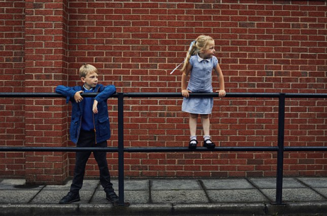 Two school children together leaning on a rail outside school
