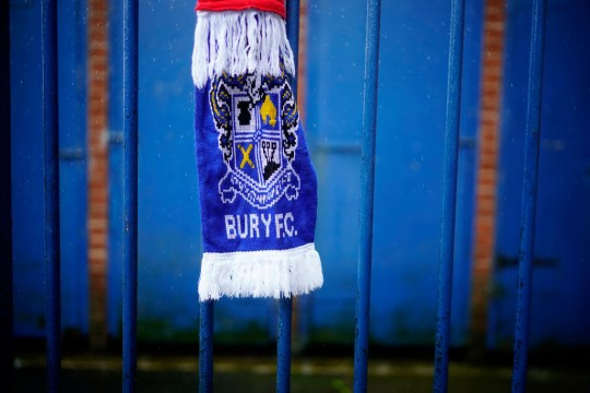 Blue Bury FC scarf hanging on gate at Gigg Stadium