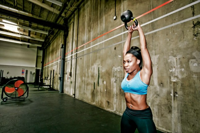 Woman working out with a kettlebell in a gym