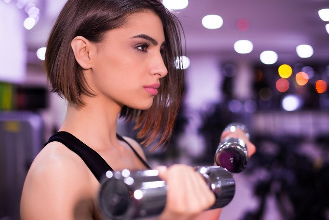 A woman wearing makeup lifting dumbbells in the gym
