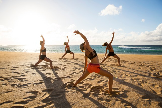 Women doing yoga on the beach