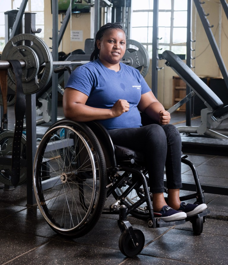 Mercy sitting in her wheelchair in the gym