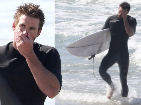 Liam Hemsworth looks distraught in the surf as ex-wife Miley Cyrus kisses Kaitlynn Carter
