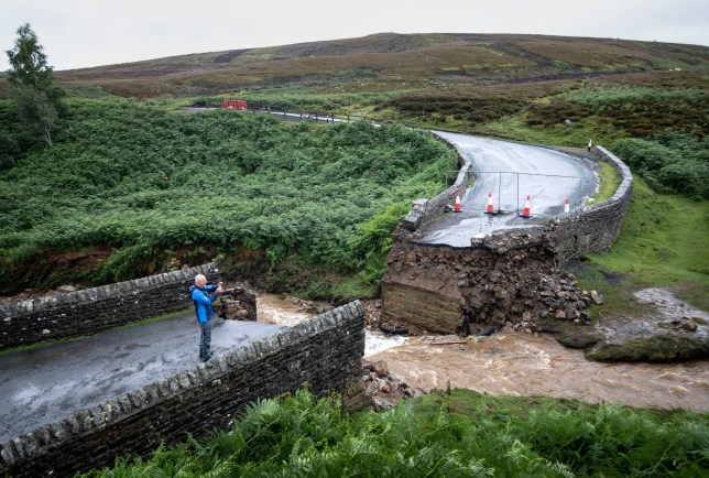 A man takes a photograph of a collapsed bridge near Grinton, North Yorkshire