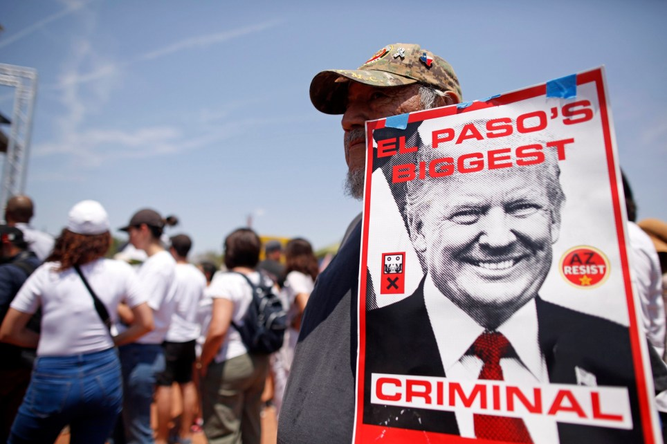Fernie Bermudez holds a sign to protest the visit of President Donald Trump to the border city after Saturday's mass shooting in El Paso, Texas, Wednesday, Aug. 7, 2019. Trump headed to El Paso, after visiting Dayton, Ohio on Wednesday to offer a message of healing and unity, but he was met by unusual hostility in both places by people who fault his own incendiary words as a contributing cause to the mass shootings. (AP Photo/Andres Leighton)