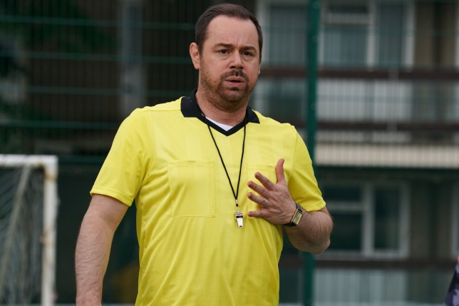Danny Dyer as Mick Carter on EastEnders, holding his chest and looking distressed