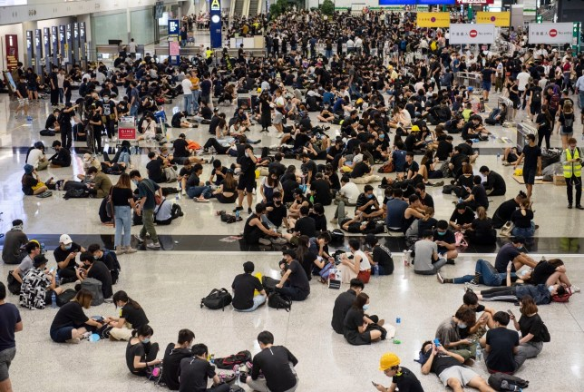 Mandatory Credit: Photo by Miguel Candela/SOPA Images/REX (10360714v) Passengers and anti-government protesters gather Protest at Hong Kong International Airport, China - 12 Aug 2019 In response from the weekend violence which a woman was shot in the eye with a projectile during the confrontations between protesters and police, anti-government protesters occupied Hong Kong's International airport and forced the cancellation of all flights.