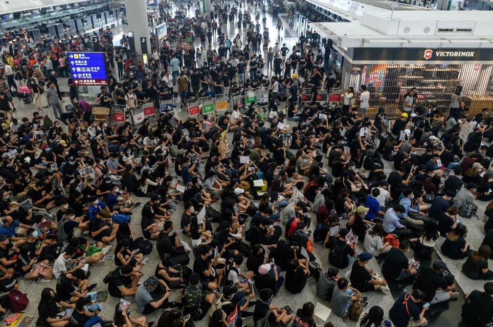 Hong Kong pro-democracy protesters (bottom) block access to the departure gates during another demonstration at Hong Kong's international airport on August 13, 2019. - Protesters blocked passengers at departure halls of Hong Kong airport on August 13, a day after a sit-in forced authorities to cancel all flights to and from the major international hub. (Photo by Philip FONG / AFP)PHILIP FONG/AFP/Getty Images