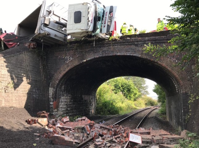A driver was rescued from a lorry suspended over a railway line
