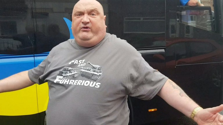 "A foul-mouthed, overweight motorist with a 'Big Oaf' number plate who told a coach driver to ""get a proper job"" has been dubbed 'the new Ronnie Pickering'. See SWNS story SWLEstandoff. The un-named VW Arteon driver - wearing a large 'Fast and Fuhrerious' T-shirt - flew into a rage after finding he couldn't pass a coach down a narrow road. Both drivers then refused to to back-down which led an hilarious 15-minute stand-off in which the 'Big Oaf' launched into a foul-mouthed tirade filmed by a stander. The furious Volkswagen driver, whose identity isn't known, exited his vehicle and launched a volley of abuse through the coach window at the stunned driver. He can be heard saying ""get a proper job and shut your mouth"" to the coach driver and calling him ""f*****g scum"". When the coach driver asks what a proper job is, the other man says ""my job"", before saying that he owns his own business. The 'businessman', who was driving a racy Volkswagen Arteon, then gets his camera phone out and takes a picture of the coach driver with both thumbs up. He was wearing a grey T-Shirt with pictures of two tanks alongside the words 'Fast and Fuhrerious', which is a reference to Adolf Hitler, who was Fuhrer of Germany. When the coach driver asks, ""why are you being abusive?"", the other man says, ""because I can be"". The standoff eventually comes to an end when the coach driver backs up and makes way for the furious Volkswagen driver."