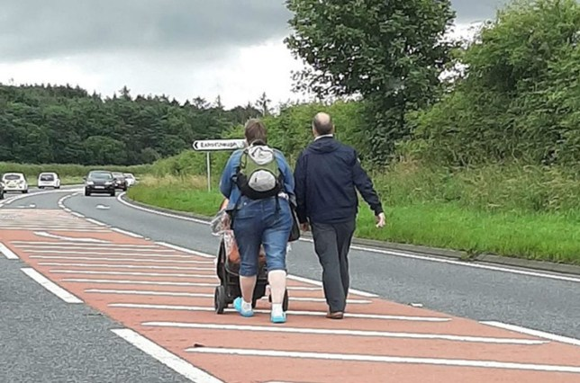 Couple stroll down middle of A1 pushing child in buggy