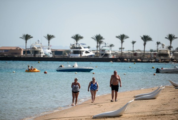 Tourists walk along the beach in Egypt's Red Sea resort of Hurghada on February 19, 2018. Egypt is seeing a promising rebound in tourism following devastating jihadist attacks, in welcome news to the government of the president as he seeks re-election this month. / AFP PHOTO / MOHAMED EL-SHAHED (Photo credit should read MOHAMED EL-SHAHED/AFP/Getty Images)