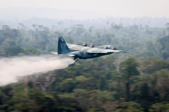 A military plane flying over the Amazon rainforest