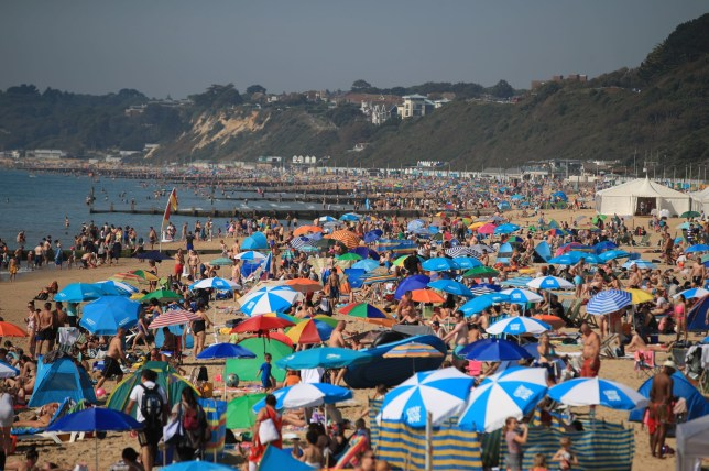 People on Bournemouth Beach enjoy the sunshine which is set to continue throughout the long weekend, with even hotter temperatures expected, possibly reaching a record high of 33C, most likely in the south-east of England, on Monday. PRESS ASSOCIATION Photo. Picture date: Sunday August 25, 2019. See PA story WEATHER Hot. Photo credit should read: Adam Davy/PA Wire