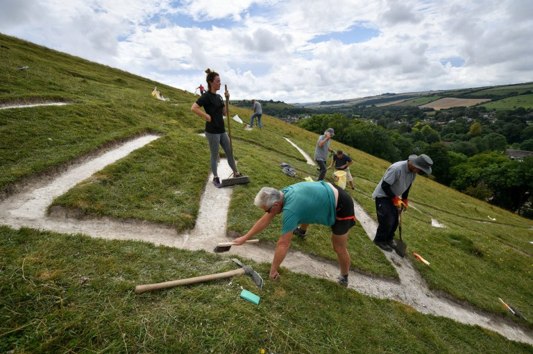 Embargoed to 0001 Thursday August 29 Volunteers work an the ribs as they refresh the Cerne Abbas Giant in Dorset, where people are working with the National Trust to re-chalk the giant figure that is thought to have been on the hillside since the 17th century and will be renovated by hand by dozens of volunteers over the next two weeks since its last refresh in 2008. PRESS ASSOCIATION Photo. Picture date: Wednesday August 28, 2019. See PA story HERITAGE Giant. Photo credit should read: Ben Birchall/PA Wire
