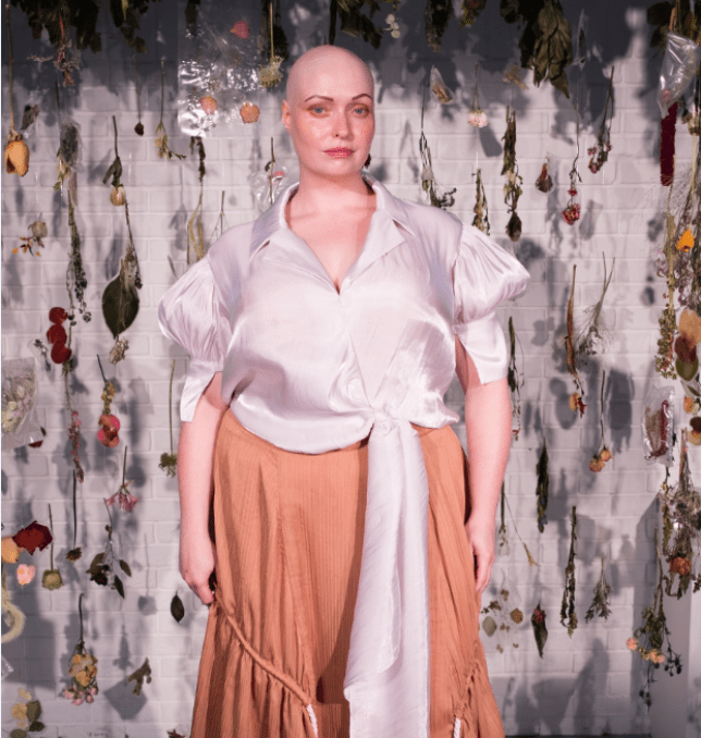 Brenda posing in a silk blouse and orange skirt