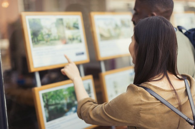 A couple looking at properties in the window of an estate agents
