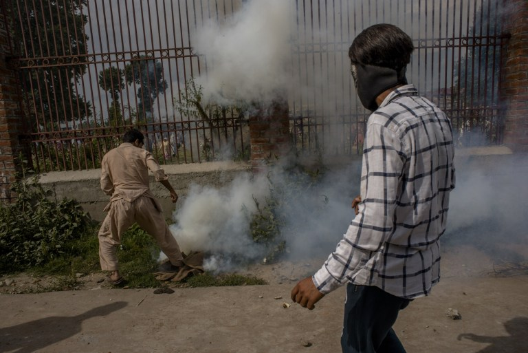 SRINAGAR, KASHMIR, INDIA - AUGUST 30: Kashmiri Muslim protesters try to douse an erupting teargas shell during a protest against Indian rule and the revocation of Kashmir's special status, on August 30, 2019 in Srinagar, the summer capital of Indian administered Kashmir, India. Dozens of Kashmir Muslim protesters were wounded in the Aanchar aera of Srinagar the summer capital of Indian administered Kashmir, after Indian government forces fired metal pellets and teargas shells at them when they were protesting against Indian rule and revocation of Kashmiri's special status. Indian authorities have deployed its thousands of government forces in Kashmir for the last four weeks after India revoked articles 370 and 35A, media face a continued communications blackout, as the lockdown enters its fourth week. Article 35A of the Indian Constitution was an article that empowered the Jammu and Kashmir state's legislature to define permanent residents of the state and provided special rights and privileges to those permanent residents, also preventing non-locals from buying or owning property in the state. Prior to 1947, Jammu and Kashmir was a princely state under the British Empire. It was added to the Constitution through a Presidential Order. The Constitution Order 1954, (Application to Jammu and Kashmir) was issued by the President of India on 14 May, 1954 in accordance with Article 370 of the Indian Constitution, and with the concurrence of the Government of the State of Jammu and Kashmir. Kashmir has been a state under siege, with both India and Pakistan laying claim to it. Human rights organizations say more than 80,000 have died in the two decade long conflict with the Indian government claiming the number as 42,000. (Photo by Yawar Nazir/ Getty Images)