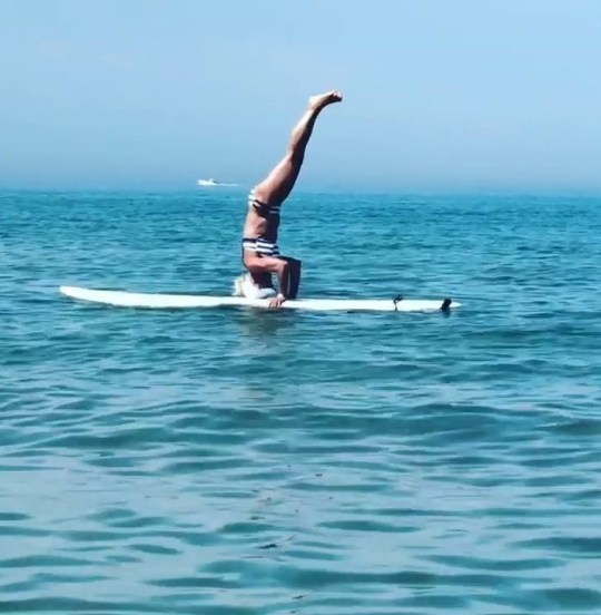 Grandma of 11 doing a headstand on a surfboard