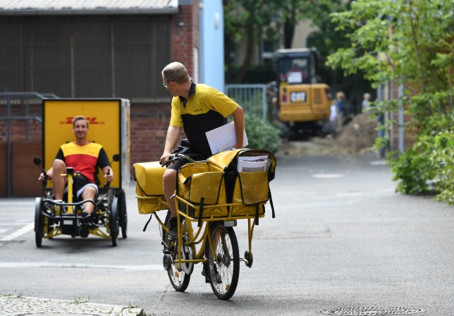A German postman on a bike meets a German parcel delivery service courier with an E-Cargobike in Berlin, Germany, August 30, 2019. Picture taken August 30, 2019. REUTERS/Annegret Hilse