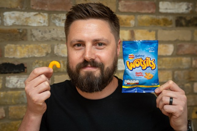 "Andy Stubbs who has been left let down by Walkers after opening a packet of Wotsits and discovering only one Wotsit in the bag, Sidcup, London. See SWNS story SWOCwotsit. A dad-of-two was left scratching his head wondering 'Wotsit all about' as he opened a bag of Wotsits - which only had ONE crisp inside. Andy Stubbs, 43, bought a multipack for a lunch in June with his family at home in Sidcup, Kent, when he reached for the cheesy flavour corn puffs. The software developer was bemused when he felt the bag - taut with air - and shook it, only to feel what felt like one wotsit inside. He held the bag over his head and shook it to make his payroll manager wife Jane, 39, and two sons - Oscar, nine, and Harry, five - laugh. Though his youngest Harry was desperate to open the bag and eat whatever was inside, Andy decided to hold onto it ""as a memento"". Andy was nudged by Jane to open the bag, though, when she read in the news the story of 41-year-old Steve Smith, who found one baked bean in a Heinz tin. Then the family gathered round the kitchen island table for the moment Andy opened the bag on Saturday (7), ""a perfectly-shaped wotsit fell out""."