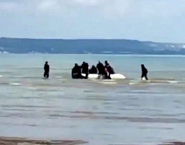 Video grab of a group of migrants coming ashore on Greatstone beach in Littlestone, Kent, after crossing the Channel . The group are some of a 100 that reportedly reached British waters yesterday. September 10 2019. See National News story NNmigrants. A flotilla of dinghies carrying almost 100 migrants made it to British waters yesterday (Weds), including one small boat that landed with 19 people on board. Border Force ships intercepted four boats carrying migrants on the busiest day for incursions this year - but missed two others that landed on the south coast. The 92 foreign men, women and children are being processed by Border Force officers at a makeshift centre in Dover, Kent, as officials struggle to deal with increased numbers of migrant incursions. At Greatstone beach, in Littlestone, Kent, the Border Force detained 19 people who managed to land after crossing the Channel.