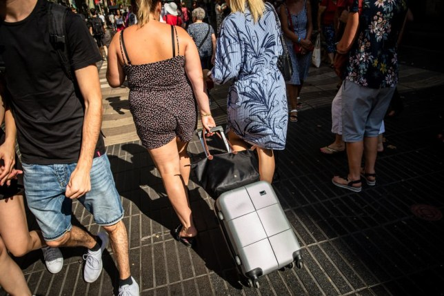 A tourist wheels a trolley suitcase along Las Ramblas Avenue in Barcelona, Spain, on Wednesday, Sept. 4, 2019. Sterlings decline has made U.K. travelers even more price sensitive this summer holiday season, pushing some to choose cheaper beach destinations in Turkey, Egypt and Tunisia. Photographer: Angel Garcia/Bloomberg via Getty Images