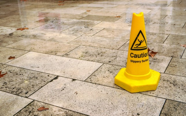 Yellow cone with caution slippery surface sign, on wet pavement tiles..