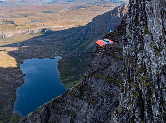 Sam Percival, 35 jumps from Lord Berkeley?s Seat in An Teallach, in the Scottish Highlands before a gust of winds takes him into the side of the mountain. See SWNS copy SWSYjump: A base jumper is lucky to be alive after he tumbled 180ft down a mountain when a gust of wind slammed him into a notorious rock face. Sam Percival, 35, miraculously survived the horror fall after his parachute spun, slamming him into the sheer cliff face at speeds of at least 30mph. He was attempting to become the first person to jump off Lord Berkeley?s Seat in An Teallach, in the Scottish Highlands - which has claimed the lives of THREE walkers this year alone. A shocking video shows how while he free-fell 200ft, a gust of wind spun him round into the cliff face, partially deflating his parachute.